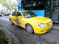 Taxi driving alongside bus a yellow drives a transporting people to their destination Royalty Free Stock Photo