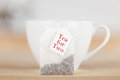 Tea bag with text and cup on table closeup of Stock Photography