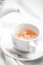 Tea being poured into tea cup on white table cloth background Stock Image