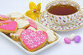 Tea and biscuits served in an antique cup with heart shaped cookies Stock Image