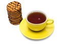 Tea with cookies in yellow teacup on white Royalty Free Stock Images
