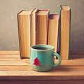 Tea cup with Christmas tree and old books over blur background Royalty Free Stock Photo