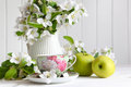 Tea cup with flower blossoms and green apples Stock Photo