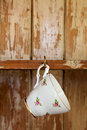 Tea cup hanging on a hook in old wooden cupboard Royalty Free Stock Photography