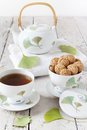 Tea on cup with teapot and amaretti sweets on white table Royalty Free Stock Photo
