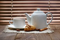 Tea cup with teapot on old wooden table against the background of blinds Royalty Free Stock Images