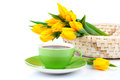 Tea cup with yellow tulips bouquet of fresh on white background Stock Images