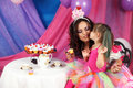 Tea and cupcake party kiss special moment when cute toddler girl giving a to mom at her Stock Images