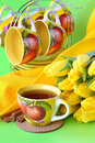 Tea cups yellow tulips green background Stock Photo