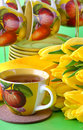 Tea cups yellow tulips green background Stock Image