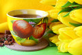 Tea cups yellow tulips green background Royalty Free Stock Photo