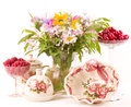 Tea in elegant cups, raspberry and flowers Royalty Free Stock Photography