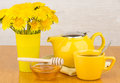 Tea with honey, teapot and bouquet of yellow flowers Royalty Free Stock Photo