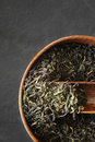 Tea leaves on the wooden bowl on the dark stone background vertical