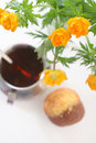 Tea with muffin and a globeflower Royalty Free Stock Photo