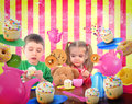 Tea party children with food are playing at a table snack cookies and teapots for a friendship and imagination concept Royalty Free Stock Photography