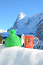 Tea pot in the cap and a cup against alpine scenery Stock Photos
