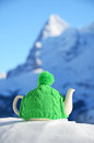Tea pot in the knitted cap on snow Royalty Free Stock Photos