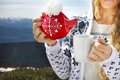 Tea pot in the knotted cap and cup in the hands of a woman against mountain scenery Royalty Free Stock Photography