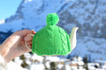 Tea pot in the knotted cap hand againstmountain scenery Stock Photo