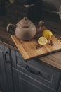 Tea pot and lemons in rustic grey kitchen interior. Slow living in country house concept Royalty Free Stock Photo