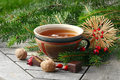 Tea in a pottery cup with christmas decoration and goodies straw star pine branches rose hips walnuts chocolate Stock Photography