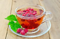 Tea with raspberry and leaf in a cup on board Royalty Free Stock Photo