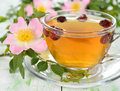 Tea with rosehip in a glass cup on white table Stock Images