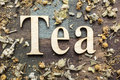 Tea time concept words and dry mountain leaves on wooden background Stock Images