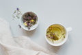 Tea time. Cup of hot herbal tea and dry tea on the gray background, top view Royalty Free Stock Photo