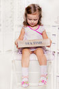 Tea time cute little girl holding a wooden box with bags Stock Image
