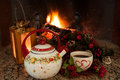 Tea time in front of the fireplace nice warm atmosphere during winter holidays teapot decorated with christmas symbols and cup Stock Photo