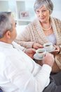 Tea time portrait of mature men and his wife drinking and interacting Stock Image