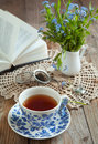 Tea time selective focus a cup of and book and spring flowers on wooden table Royalty Free Stock Photos