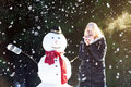 Tea time with a snowman pretty blond girl dinking outdoors while it s snowing Stock Photography