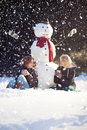 Tea time with a snowman two young women sitting near and drinking hot while it s snowing Stock Photo