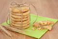Tea time white chocolate chip cookie stack tied with string with half eaten biscuit and ears of wheat over green serviette and oak Royalty Free Stock Photo