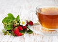 Tea and wild strawberries cup of on a wooden background Stock Images