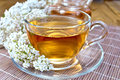 Tea with yarrow in cup on bamboo napkin Royalty Free Stock Photo