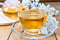 Tea with yarrow in cup on board Royalty Free Stock Photo