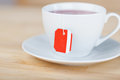 Teabag in a cup of tea with blank red label hanging to the front plain white teacup Royalty Free Stock Photo