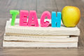 Teach concept in foam letters on a pile of text books Stock Photography