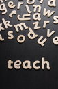 Teach in wooden letters spell the word on a blackboard Royalty Free Stock Image