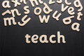 Teach in wooden letters the word on a blackboard surface Stock Image