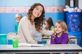 Teacher with arm around little girl in classroom portrait of beautiful young kindergarten Royalty Free Stock Photos