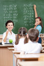 Teacher asks pupils at the chalkboard Royalty Free Stock Photo