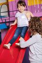 Teacher assisting girl while playing on slide young little in kindergarten Royalty Free Stock Photos