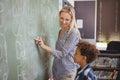 Teacher assisting schoolboy in writing alphabet on chalkboard