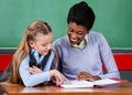 Teacher assisting schoolgirl at desk young african american female in classroom Stock Photos