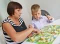 Teacher and boy playing with table game a little of dof Royalty Free Stock Photo